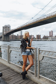 USA, New York City, Brooklyn, young woman standing at the waterfront eating an ice cream - BOYF01155