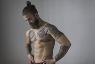 Portrait bare chested man with tattoos and beard - CAIF22356