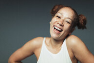 Portrait carefree woman with freckles laughing - CAIF22377
