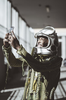 Happy astronaut in spacesuit using smartphone - JCMF00021