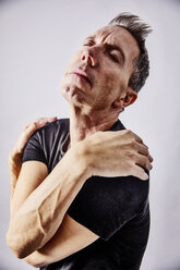 Portrait of egocentric mature man hugging hisself - JATF01113