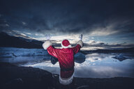 Iceland, rear view of a man disguised as Santa Claus standing at a glacier raising his arms - OCMF00167