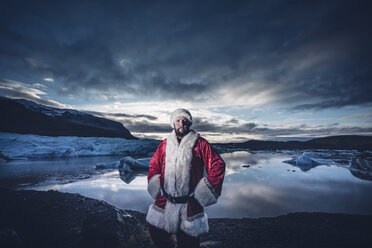 Iceland, portrait of a man disguised as Santa Claus standing at a glacier - OCMF00170