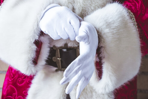 Santa Claus putting on his white gloves, close-up - JCMF00030