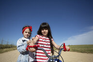 Two girls with bicycle on path in remote landscape - ERRF00176