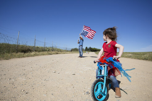 Girl with bicycle and man with American flag on path in remote landscape - ERRF00182