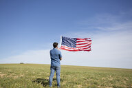 Man with American flag standing on field in remote landscape - ERRF00185