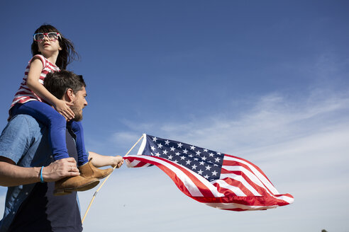Man with daughter and American flag under blue sky - ERRF00191