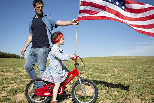 Man and daughter with bicycle and American flag on field in remote landscape - ERRF00200