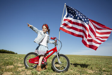 Girl with bicycle and American flag on field in remote landscape - ERRF00203