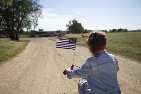 Girl with American flag riding bicycle on path in remote landscape - ERRF00206