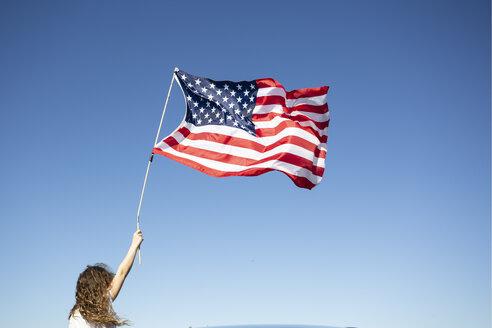 Girl holding American flag under blue sky - ERRF00209