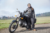 Full length portrait of female biker wearing leather jacket while standing by motorcycle on dirt road - CAVF57472