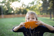 Portrait of girl holding carved pumpkin while standing in yard during Halloween - CAVF57496