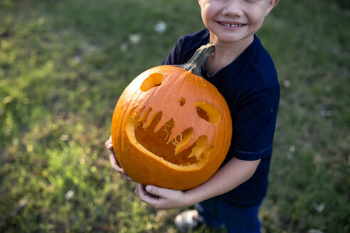 Low section of boy holding jack o lantern while standing on field in yard - CAVF57499