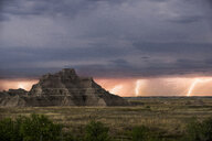 Scenic view of rock formations at Badlands National Park against thunderstorm and lightning - CAVF57505
