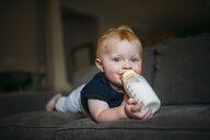 Portrait of cute baby boy drinking milk from bottle while lying on sofa at home - CAVF57547