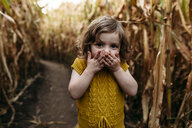 Portrait of girl with hands covering mouth standing in farm - CAVF57559