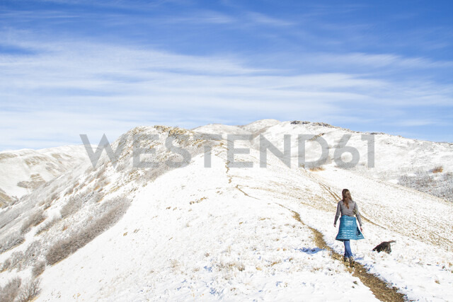 Rear view of woman walking on mountain against cloudy sky during winter - CAVF57562