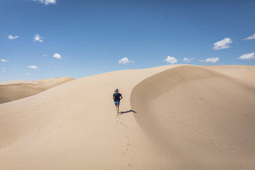 High angle view of woman walking on sand at Great Sand Dunes National Park during sunny day - CAVF57574