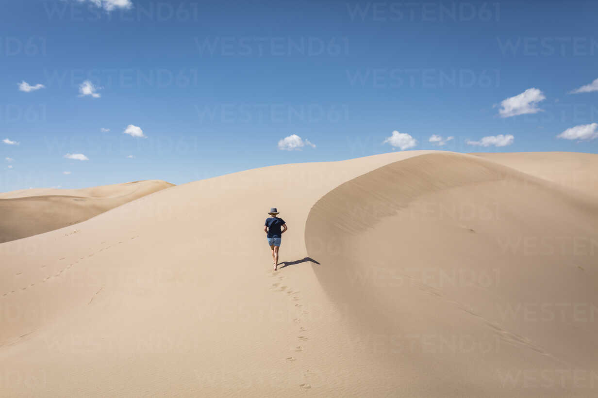 High angle view of woman walking on sand at Great Sand Dunes National Park during sunny day - CAVF57574 - Cavan Images/Westend61