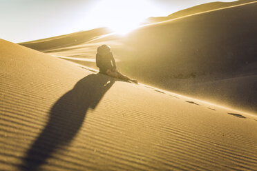 Woman sitting on sand dune at national park during sunset - CAVF57577