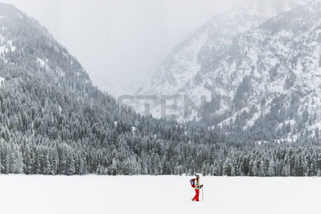 Side view of woman with backpack hiking on snow covered field - CAVF57580