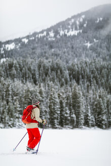 Woman with backpack hiking on snow covered landscape - CAVF57583