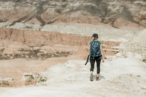 Rear view of female hiker with backpack walking at desert - CAVF57589