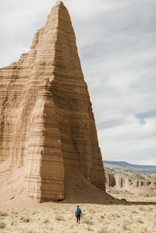 Rear view of hiker by rock formations at desert - CAVF57592