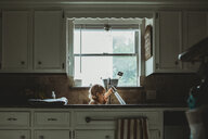 Playful girl playing with faucet while sitting against window in kitchen sink at home - CAVF57613