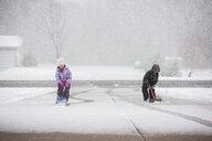 Siblings shoveling snow at driveway during snowfall - CAVF57619