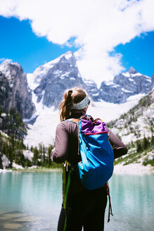 Rear view of female hiker carrying backpack by lake against mountains at Grand Teton National Park - TGBF01790