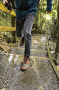 Male hiker splashing water while running up stairs in forest - TGBF01877
