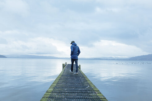 Rear view of young man walking on pier over lake - TGBF01880