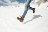 Low section of man in jeans running on snow - TGBF01883