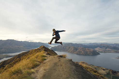 Full length of young man jumping on mountain against sky - TGBF01886