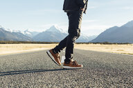 Low section of young man walking on country road against mountains on sunny day - TGBF01898
