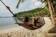 Young woman resting in hammock at beach - CAVF57666