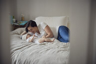 Happy mother looking at son while lying on bed at home - CAVF57693