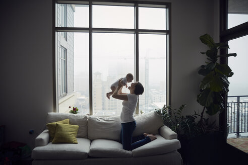Side view of happy mother playing with son while kneeling on sofa by window at home - CAVF57699