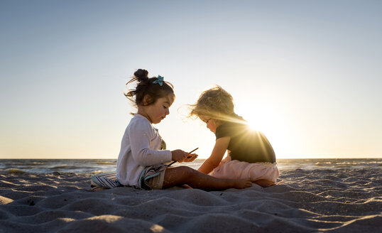 Sisters sitting on sand at beach against clear sky during sunset - CAVF57717