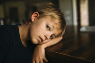 Portrait of serious boy lying head on table at home - CAVF57726