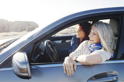 Cheerful mother and daughter looking away while sitting in car - CAVF57735