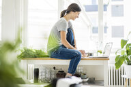 Woman sitting on kitchen table, searching for healthy recipes, using laptop - MOEF01709