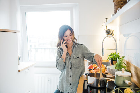 Laughing woman talking on the phone, while preparing pumpkin soup - MOEF01715