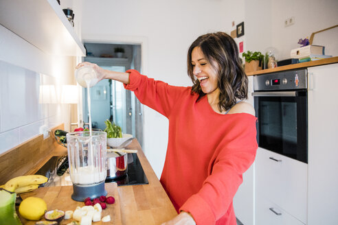 Woman prearing fruit smoothie in her kitchen - MOEF01721