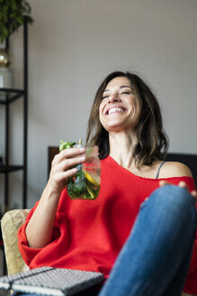 Mature woman relaxing at home, drinking lemon water - MOEF01724
