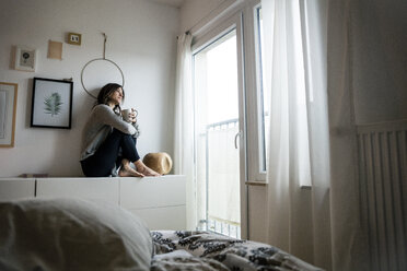 Woman sitting on chest of drawers, drinking tea, relaxing - MOEF01754