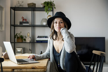 mature woman with hat, sitting at home, using laptop - MOEF01760